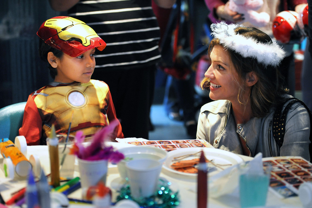 . Joshua Martinez,7, of Wilmington,left, meets with  Toyota Grand Prix of Long Beach Pro/Celebrity Race participant and actress Tricia Helfer, during a visit at the children at Miller Children�s Hospital at Long Beach Memorial Medical Center.       Long Beach Calif., Thursday, April 10,  2014.   (Photo by Stephen Carr / Daily Breeze)