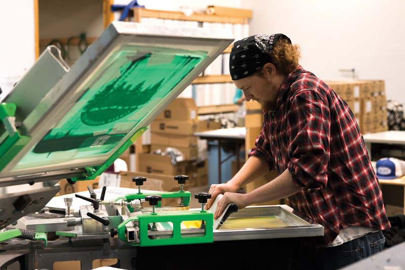 Matthew Gaston | The Sheridan Press<br>Chris Roberts spreads an even layer of yellow ink, the second layer, across the screen for a sweatshirt. Each color used in screen-printing requires its own screen. Friday, Oct. 5, 2018.