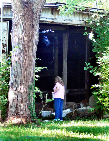 John P. Cleary | The Herald Bulletin<br /> Darla Forney, of Markleville, Checks an old abandoned building during a large ground search for missing person Larry Tucker that took place Monday in New Castle.  Forney is a cousin of Tuckers.