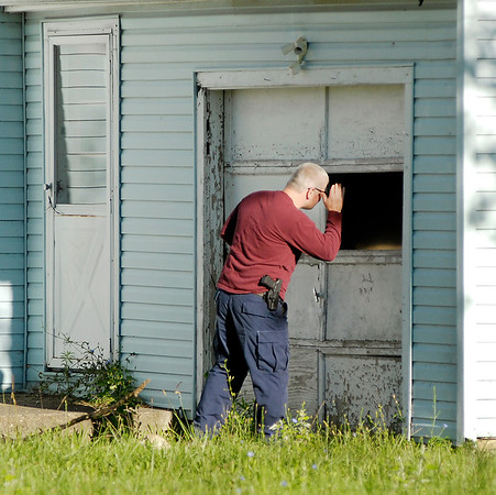 John P. Cleary | The Herald Bulletin<br /> New Castle Police Sgt. Andy Hood looks into an abandoned house along N Ave. in New Castle Monday morning during a ground search for missing person Larry Tucker.