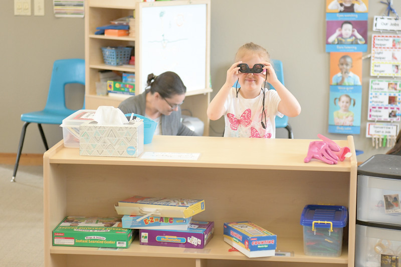 Matthew Gaston | The Sheridan Press<br>Fable Trueblood looks through a pair of binoculars at Head Start Tuesday, April 9, 2019.