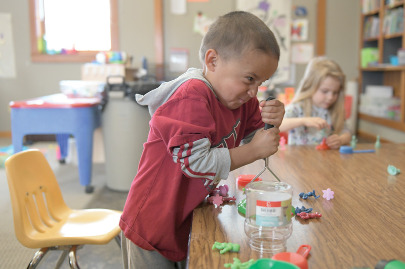 "Matthew Gaston | The Sheridan Press<br>Kaleb Beckman, 3, smooshes some slime at the science table during ""work time"" at Head Start Tuesday, April 9, 2019."
