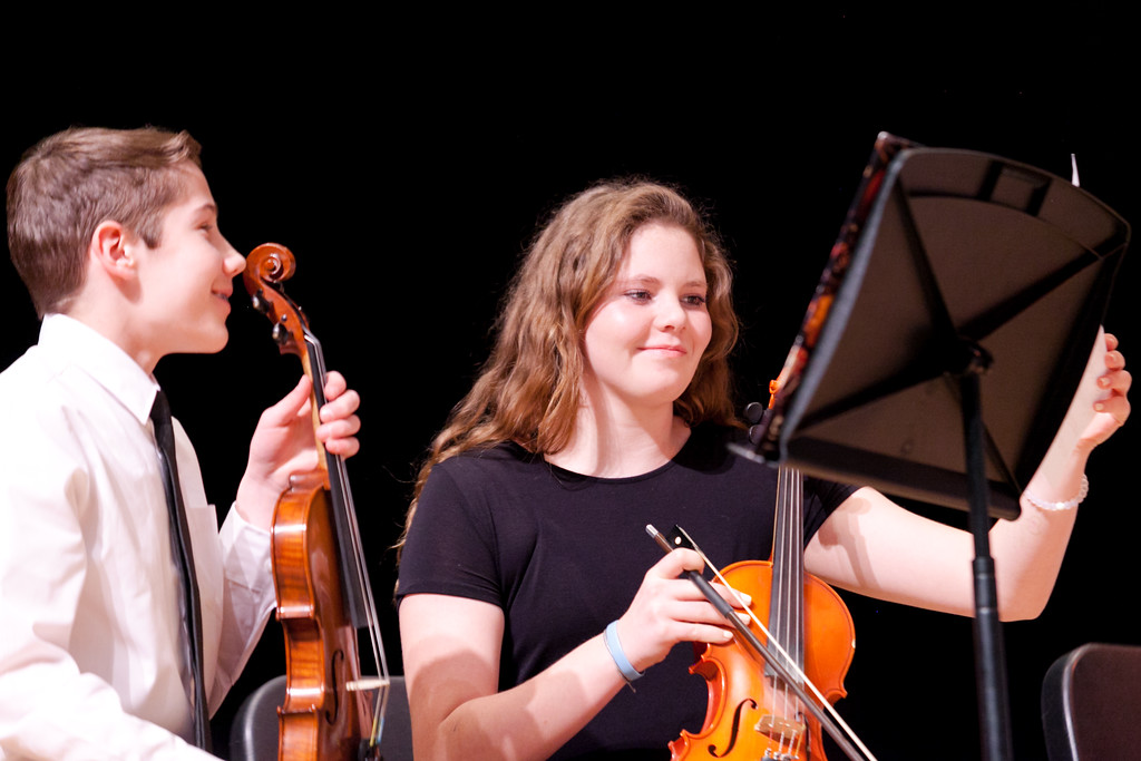 Tibby McDowell | The Sheridan Press<br /> Sebastian Kuchma, left, and Reese Anderson smile during the audience applause after performing a song during the orchestra concert at the Sheridan Junior High School Early Auditorium Wednesday, March 21, 2018.