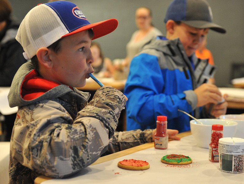 Ryan Patterson | The Sheridan Press<br /> Cheyden Kehrer, left, eats a candy cane while Tristin Kehrer decorates during a cookie decorating party hosted by The Sheridan Press at Cottonwood Kitchen + Home Friday, Nov. 23, 2018.