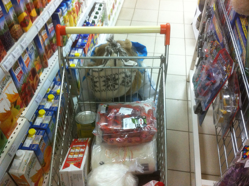 Our shopping cart. Hot dog sausages on top, a box of apple juice, and a can of corn are what you see. Underneath were some paper towels, noodles, and spaghetti sauce.