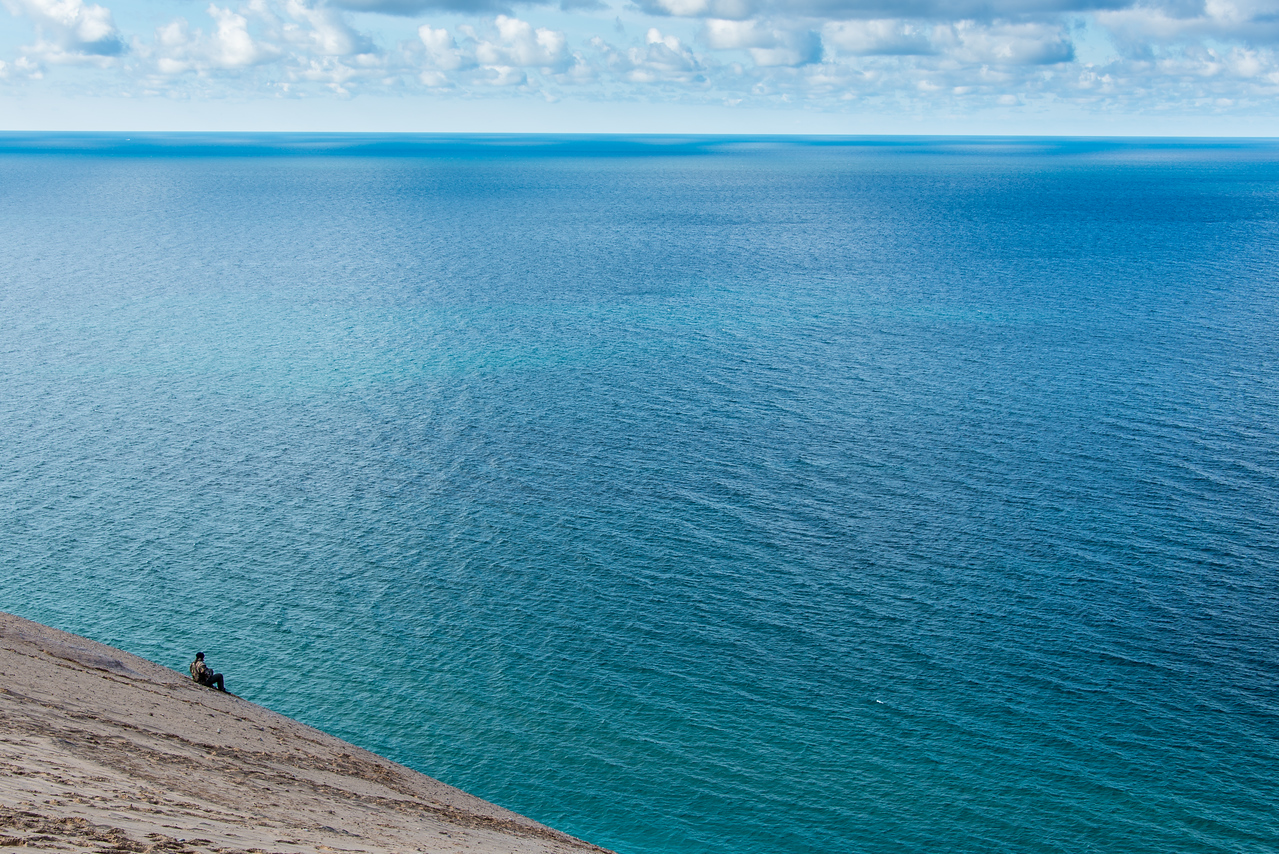 Hiker resting on very steep ascent back to top with Lake Michigan in background, Sleeping Bear Dunes, MI - October 2014