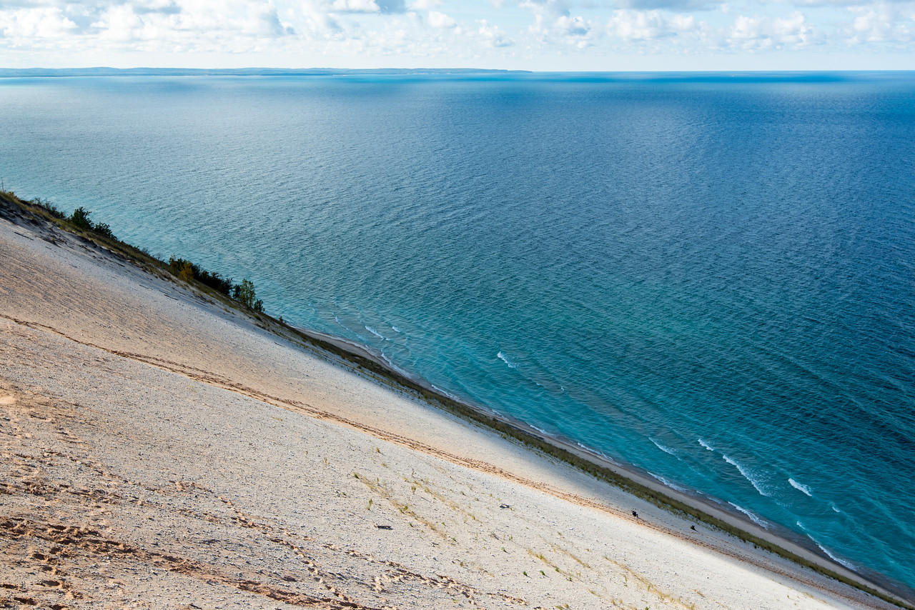 Hikers resting near bottom on dune on very steep ascent back to top with Lake Michigan in background, Sleeping Bear Dunes, MI - October 2014