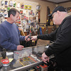 Crack Shot Guns owner Mike Clevenger shows Earl Gerholdt of Anderson a pistol at his shop recently.