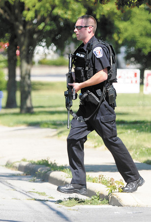 APD surrounds a home on East Fifth Street on Saturday as a stand off developed while serving a warrant.