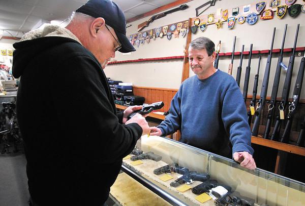 Earl Gerholdt, of Anderson, checks out a pistol as Crack Shot Guns owner Mike Clevenger assists him.  Gerholdt bought the gun.