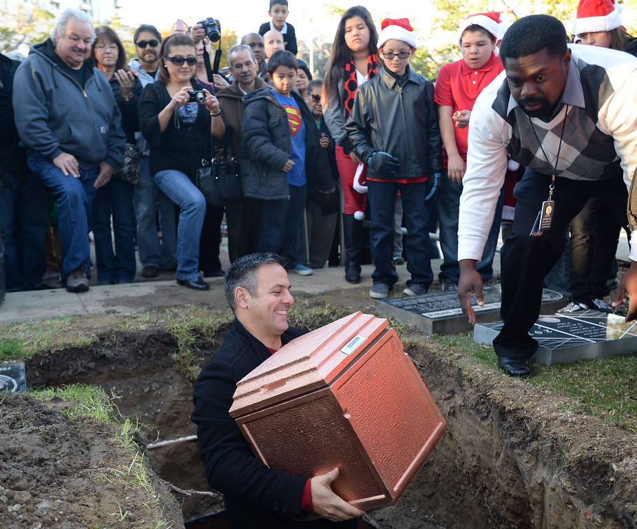 . A 25 year old time capsule was uncovered during the annual tree lighting at Pepper Tree Plaza Thursday, December 05, 2013, in San Pedro, CA. Councilman Joe Buscaino places a new time capsule that will be opened in 25 years. Photo by Steve McCrank/DailyBreeze