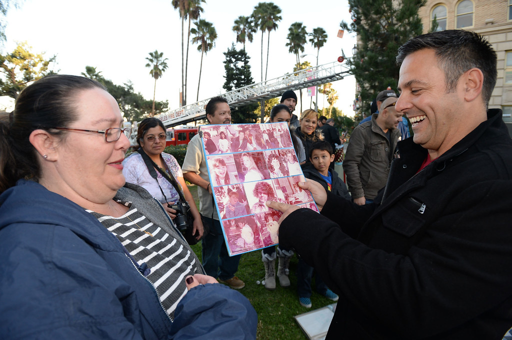 . Los Angeles City Councilman Joe Buscaino, right, and Kaare Bodlovich, left, were classmates and laugh at their pictures after it was removed from a 25 year old time capsule that was uncovered during the annual tree lighting at Pepper Tree Plaza Thursday, December 05, 2013, in San Pedro, CA.  Photo by Steve McCrank/DailyBreeze