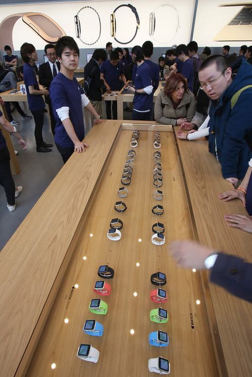 . Customers look at models of Apple Watch displayed in a glass case at an Apple Store in Tokyo as Apple Watch made its debut Friday, April 10, 2015. Customers were invited to try them on in stores and order them online. (AP Photo/Koji Sasahara)