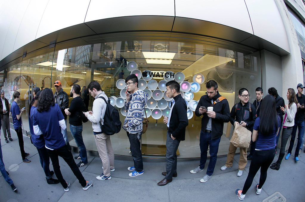 . Customers wait in line outside of an Apple store in front of a display for Apple\'s new watch in San Francisco, Friday, April 10, 2015. Apple has started taking orders for the watch on its website and the Apple Store app. Currently, that\'s the only way Apple is selling the watch, with shipments scheduled to start April 24. (AP Photo/Eric Risberg)