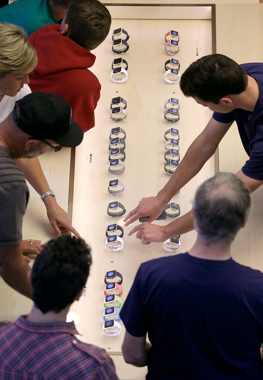 . An Apple store worker, right, shows customes Apple\'s new watches in San Francisco, Friday, April 10, 2015. Apple has started taking orders for the watch on its website and the Apple Store app. Currently, that\'s the only way Apple is selling the watch, with shipments scheduled to start April 24. (AP Photo/Eric Risberg)