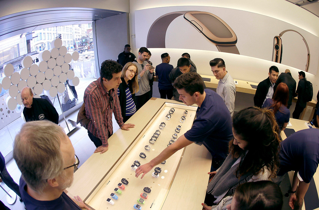 . In this photo taken with a fisheye lens, customers listen as an Apple employee points toward Apple\'s new watch, in San Francisco, Friday, April 10, 2015. Apple has started taking orders for the watch on its website and the Apple Store app. Currently, that\'s the only way Apple is selling the watch, with shipments scheduled to start April 24. (AP Photo/Eric Risberg)