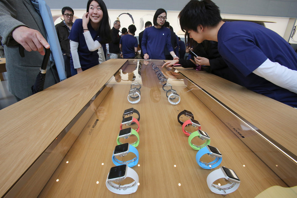 . Customers and staff look at models of Apple Watch displayed in a glass case at an Apple Store in Tokyo as Apple Watch made its debut Friday, April 10, 2015. Customers were invited to try them on in stores and order them online. (AP Photo/Koji Sasahara)