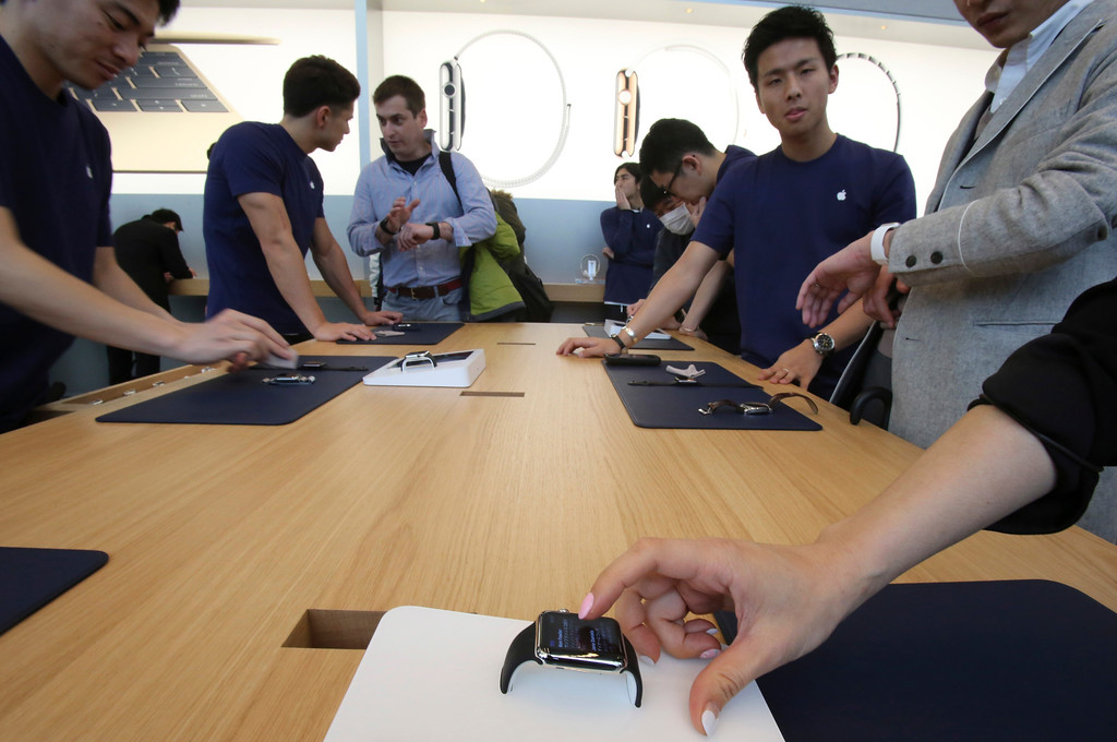 . Customers and staff demonstrate Apple Watch at an Apple Store in Tokyo as Apple Watch made its debut Friday, April 10, 2015. Customers were invited to try them on in stores and order them online. (AP Photo/Koji Sasahara)
