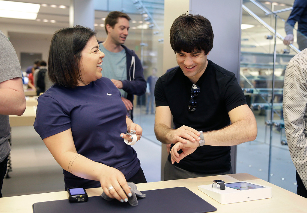 . An Apple employee, left, laughs next to a customer trying on Apple\'s new watch, in San Francisco, Friday, April 10, 2015. Apple has started taking orders for the watch on its website and the Apple Store app. Currently, that\'s the only way Apple is selling the watch, with shipments scheduled to start April 24. (AP Photo/Eric Risberg)