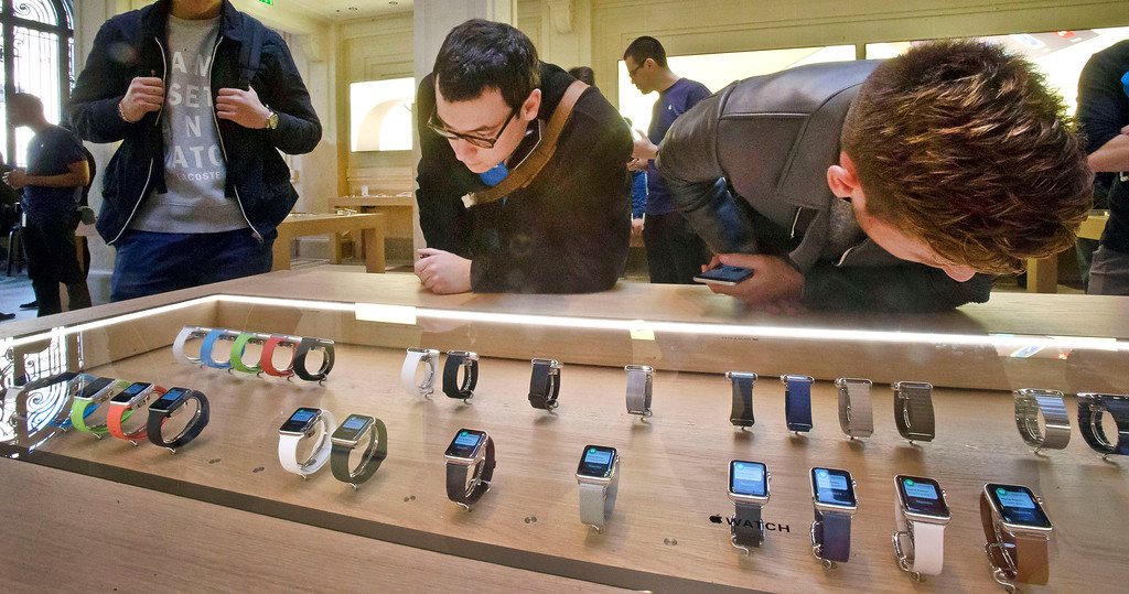 . Customers examine the new Apple watches presented at the Paris Opera Apple store Friday April 10, 2015. From Beijing to Paris and San Francisco, the Apple Watch made its world debut Friday. Customers were invited to try them on in stores and order them online. (AP Photo/Michel Euler)