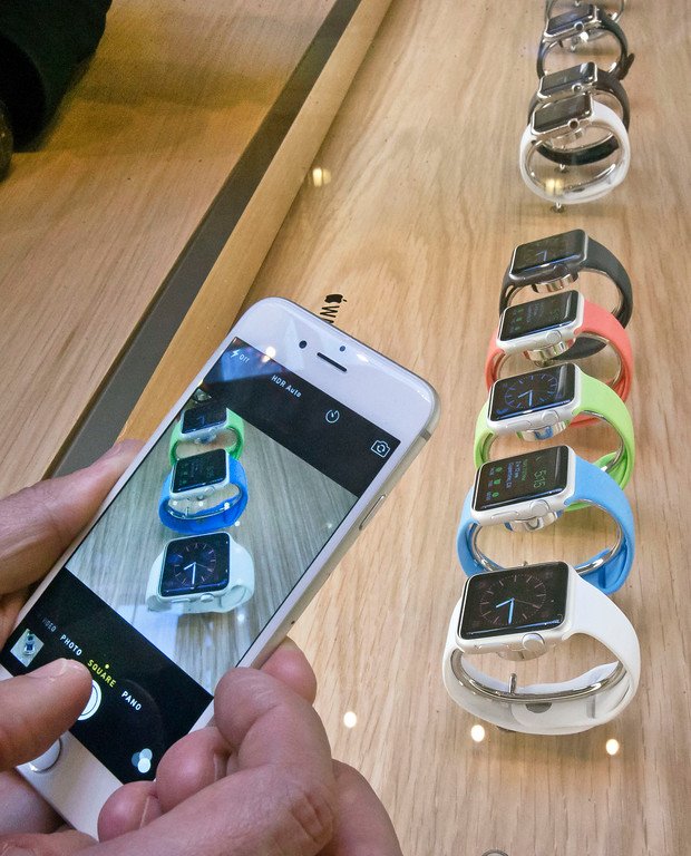 . A customer takes snapshots of new Apple watches presented at the Paris Opera Apple store Friday April 10, 2015. From Beijing to Paris and San Francisco, the Apple Watch made its world debut Friday, with customers invited to try them on in stores and order them online. (AP Photo/Michel Euler)