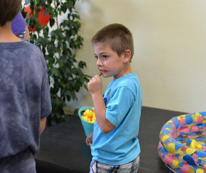 Ryan Patterson | The Sheridan Press<br /> Emmett Klepperich enjoys a caramel apple sucker at Teton Therapy's evening of entertainment Thursday, Sept. 6, 2018. The evening celebrated the company's two-year anniversary and had games and food centered around a carnival theme.