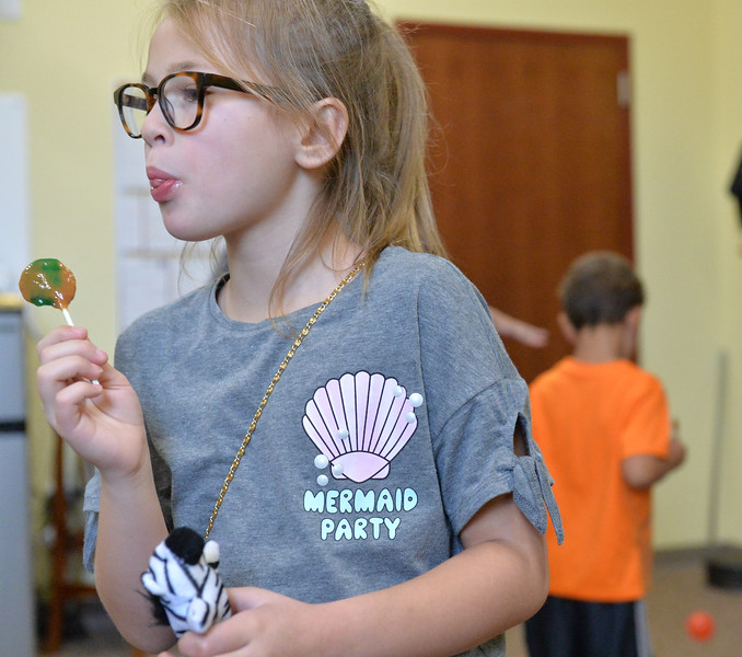 Ryan Patterson | The Sheridan Press<br /> Zoey Bougie enjoys a caramel apple sucker at Teton Therapy's evening of entertainment Thursday, Sept. 6, 2018. The evening celebrated the company's two-year anniversary and had games and food centered around a carnival theme.