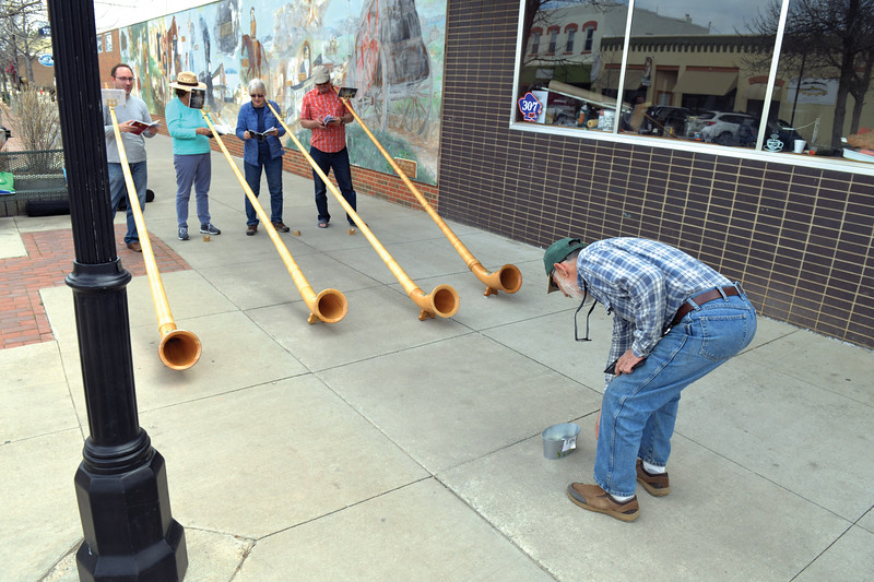 Matthew Gaston | The Sheridan Press<br> A passer-by drops a tip in the bucket after listening to a selection performed by the Big Horn Alphorns on Main Street in Sheridan Saturday, April 20, 2019.