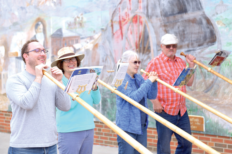 Matthew Gaston | The Sheridan Press<br>The Big Horn Alphorns, from left, Ryan Schasteen, Edre Maier, Patricia Dray and Dale Hoffmann play handmade alphorns on the corner of Grinnell Plaza and Main Street Saturday April 20, 2019.