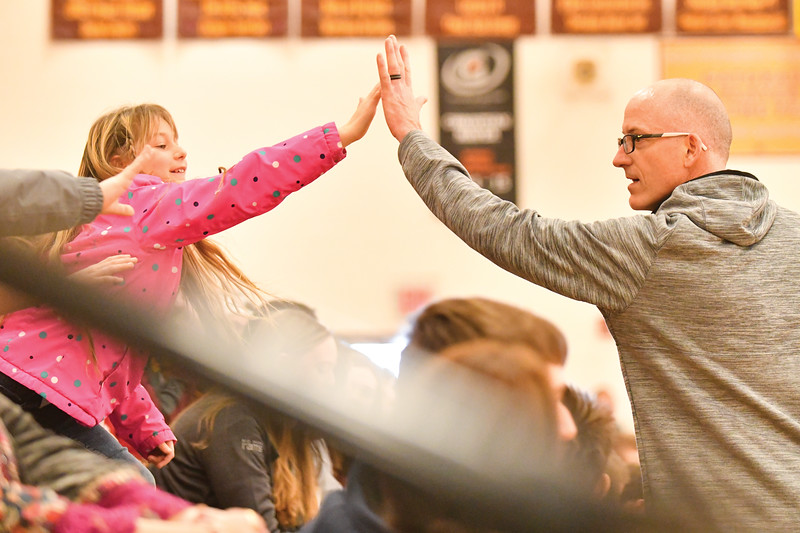 Matthew Gaston | The Sheridan Press<br>Big Horn Elementary 3rd-grader Maggie Brogdon high-fives with the Faculty basketball teams star forward, Kip Butler Thursday, Jan. 31, 2019.
