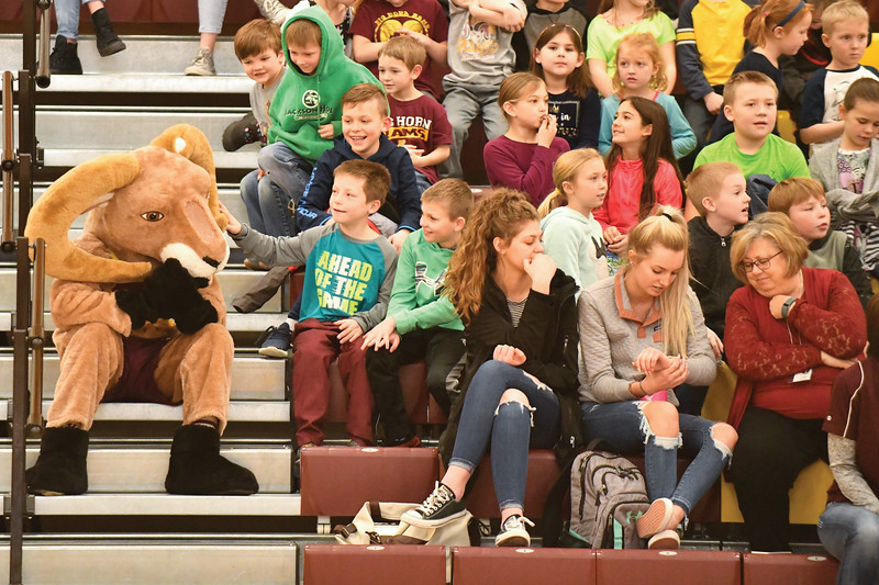 Matthew Gaston | The Sheridan Press<br>Big Horn Elementary School 3rd-grader Blaine Fancher cautiously reaches out to pet the Rams' mascot during the Senoirs verses the Fauclty game at Big Horn High School Thursday, Jan. 31, 2019.