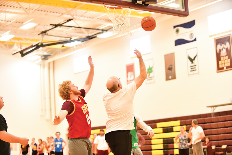 Matthew Gaston | The Sheridan Press<br>The Faculties' Justin Kidneigh flies by the Seniors Ryan Johnson (USC) for a reverse layup that NBA great Steve Nash would proud of Thursday, Jan. 31, 2019.