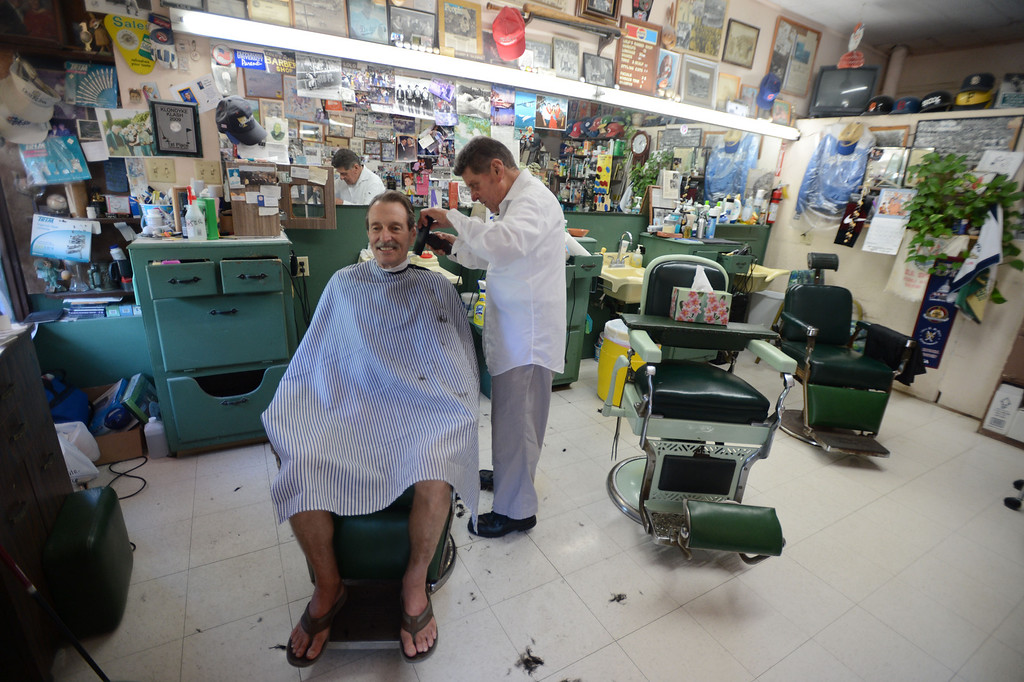 . Avalon, Calif., -- 09-04-13-  Lolo Saldana ,83, cuts the hair of boat captain Skip Odel at Lolo\'s Plaza Barber Shop in the city of Avalon, on Catalina Island. This year Avalon turns 100. Lolo was born on the Island and has many stories to tell about the Island and the was it is and the the way it used to be.    Stephen Carr/  Press-Telegram