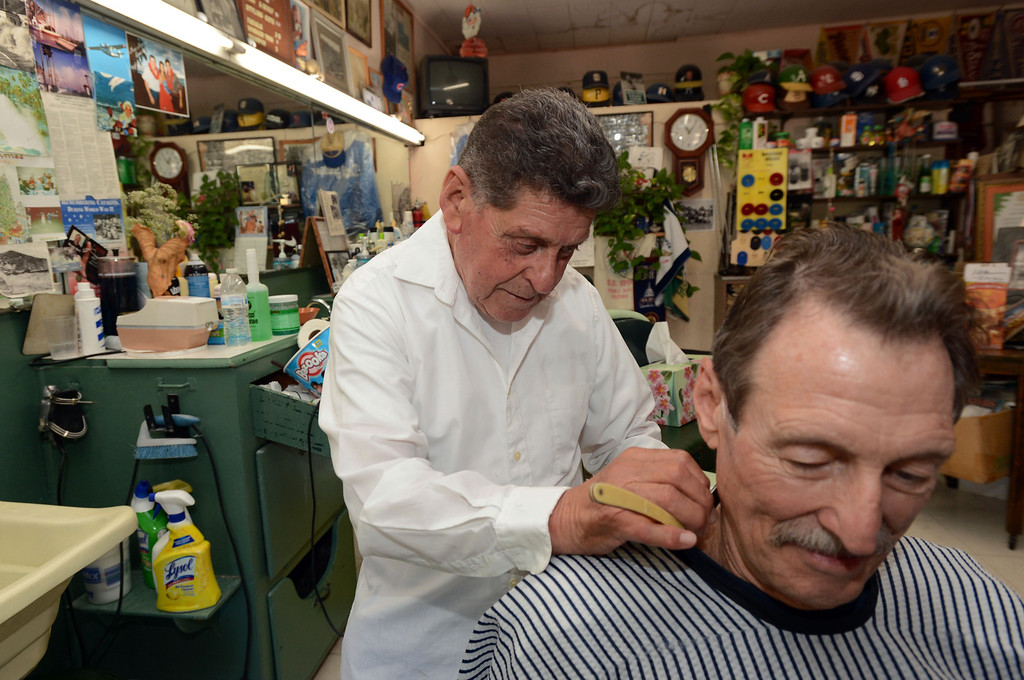 . Avalon, Calif., -- 09-04-13-  Lolo Saldana ,83, uses hot foam and a straight razor to trim the hair of boat captain Skip Odel at Lolo\'s Plaza Barber Shop in the city of Avalon, on Catalina Island. This year Avalon turns 100. Lolo was born on the Island and has many stories to tell about the Island and the was it is and the the way it used to be.    Stephen Carr/  Press-Telegram