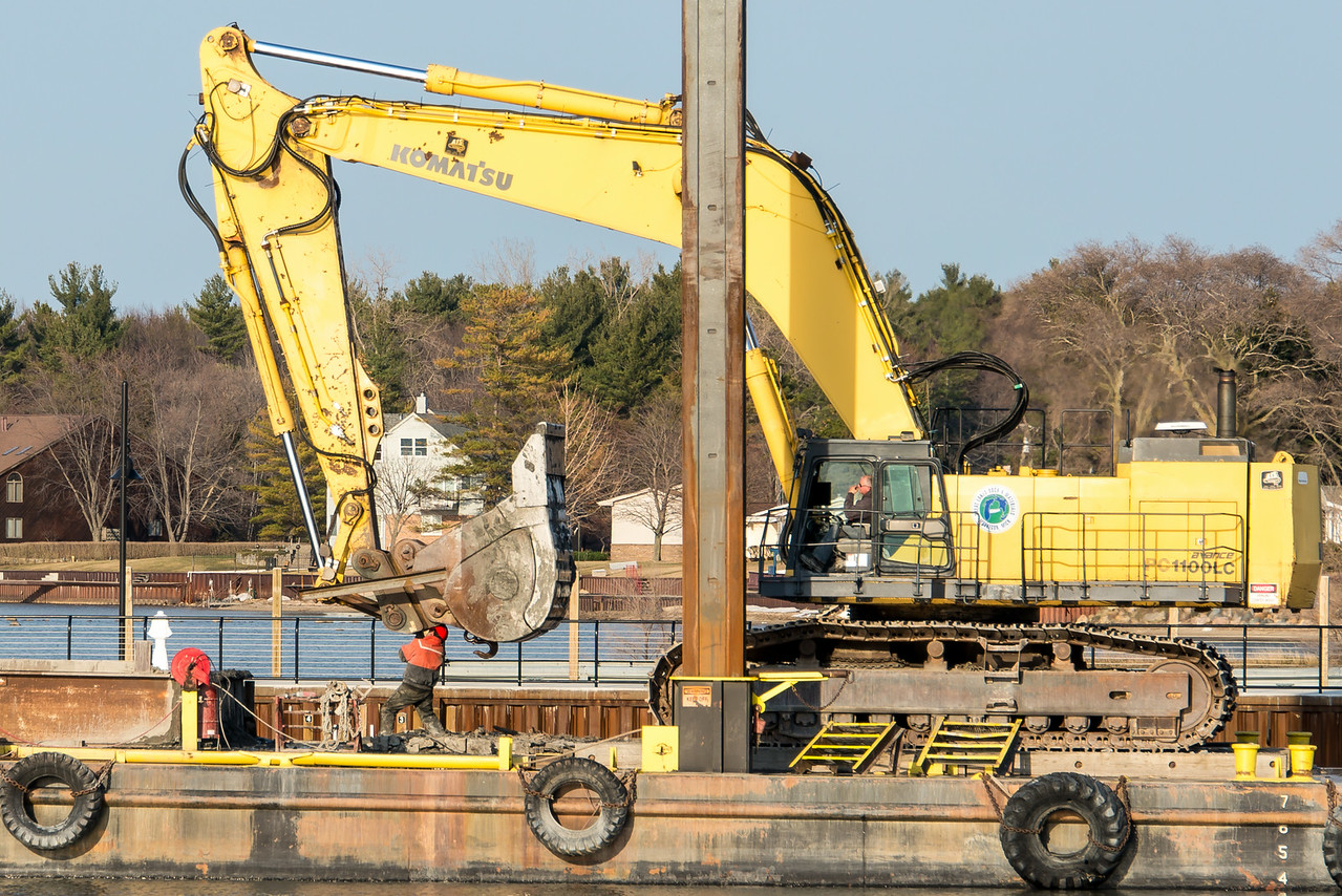 Worker adjusting boom while dredging Port Austin Harbor - April 2014