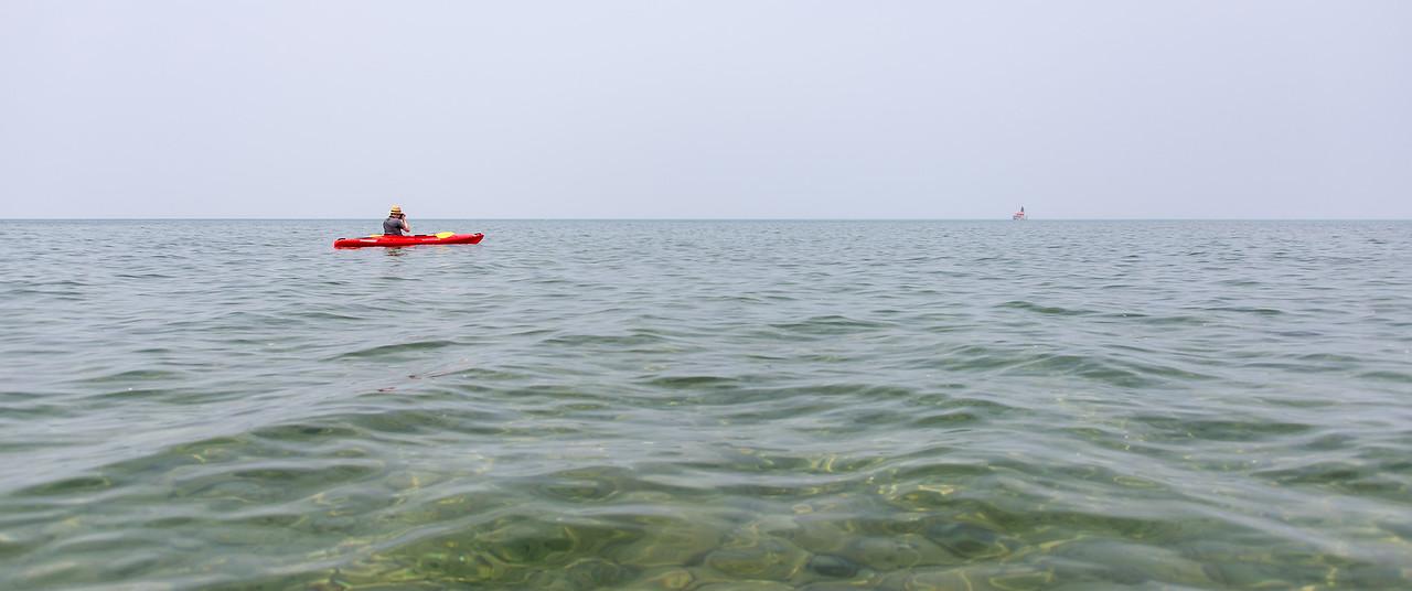 Eric taking aim at lighthouse while kayaking, July 2015