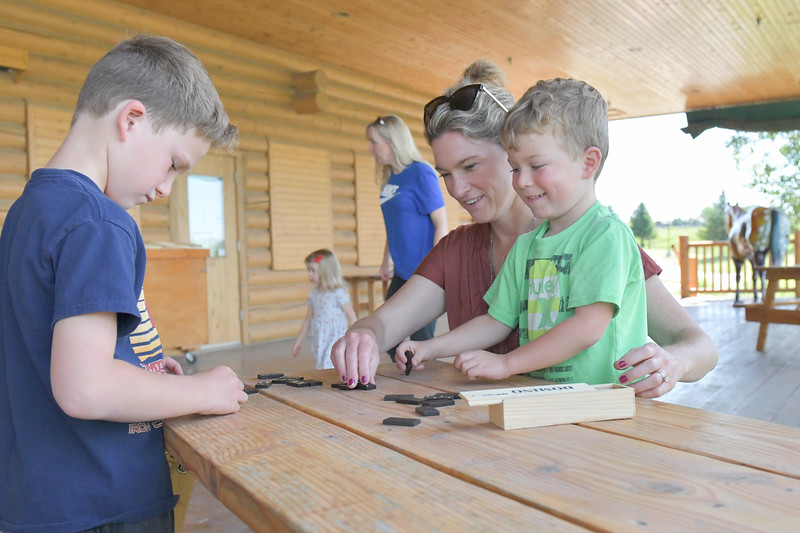 Ryan Patterson | The Sheridan Press<br /> From left: Ryan Smith, age 7, Kristin Smith and Owen Smith, age 4, play dominoes during Tidbit Tuesday at the Sheridan County Historical Society & Museum Tuesday, July 2, 2019.