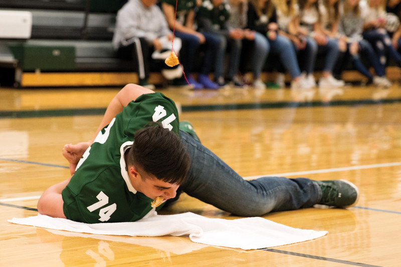 Matthew Gaston | The Sheridan Press<br>Junior Caleb Witter, goes all the way down to the floor for a no handed donut eating contest Thursday, Oct. 4, 2018.