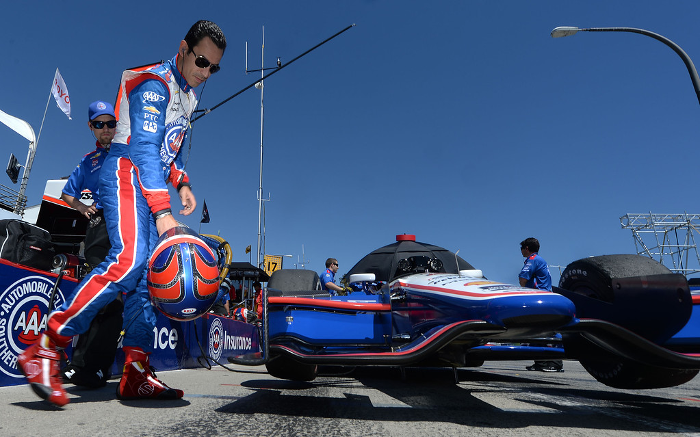 . Indycar driver Helio Castroneves compares the color of his helmet to his race car Friday afternoon April 11, 2014 prior to the second practice session at the 40th Toyota Grand Prix of Long Beach. Simon Pagenaud, from France, led drivers with the quickest lap time of the day. Qualifying for Sunday\'s race is Saturday.  (Will Lester/Inland Valley Daily Bulletin)
