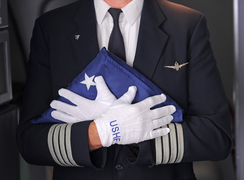 . American Airlines Captain Kriss Kliegle carries the U.S. Honor Flag off the plane as it arrives at Los Angeles International Airport in memory of TSA agent Gerardo Hernandez. It will be used at his upcoming funeral services. (Wed, Nov 6, 2013. Photo by Brad Graverson/The Daily Breeze/POOL)