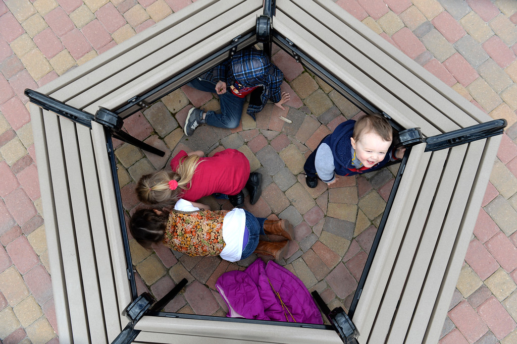 Justin Sheely | The Sheridan Press<br /> One-year-old Gabriel Watson looks up as his siblings, from top, William, Abigale and Kayla Watson play inside a circle of benches Friday at Whitney Commons. The weekend is expected to be mostly sunny with high temperatures in the mid-to-high 50s.