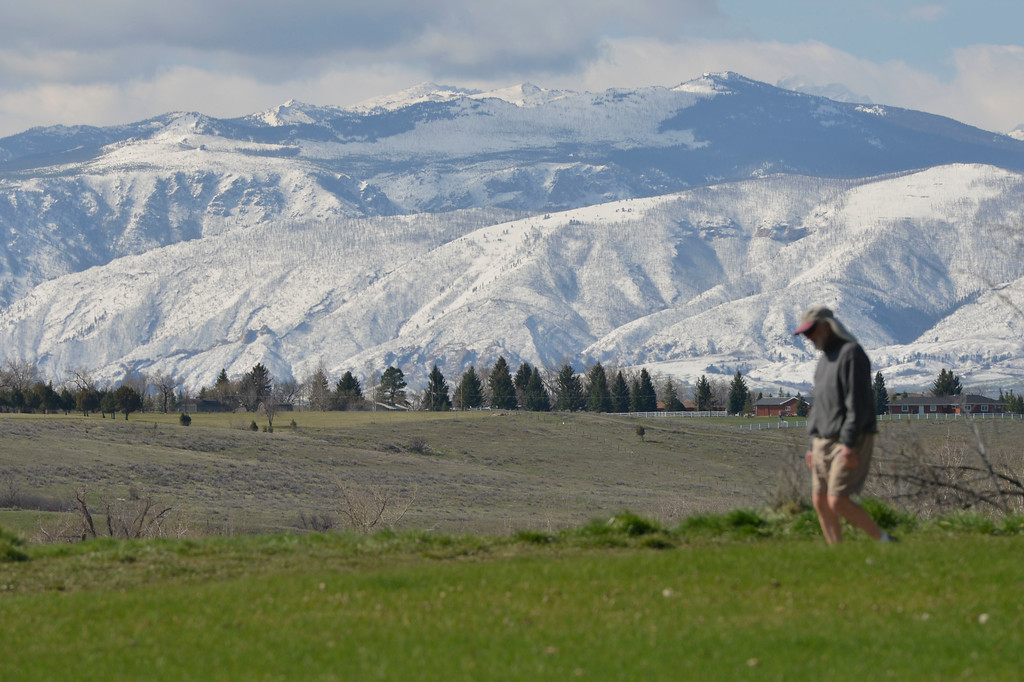 Justin Sheely | The Sheridan Press<br /> A man walks down the path on top of Kendrick Park with the Bighorn Mountains in view Tuesday morning. Thursday is expected to be warm with a high of 71, Friday and Saturday could see rain.