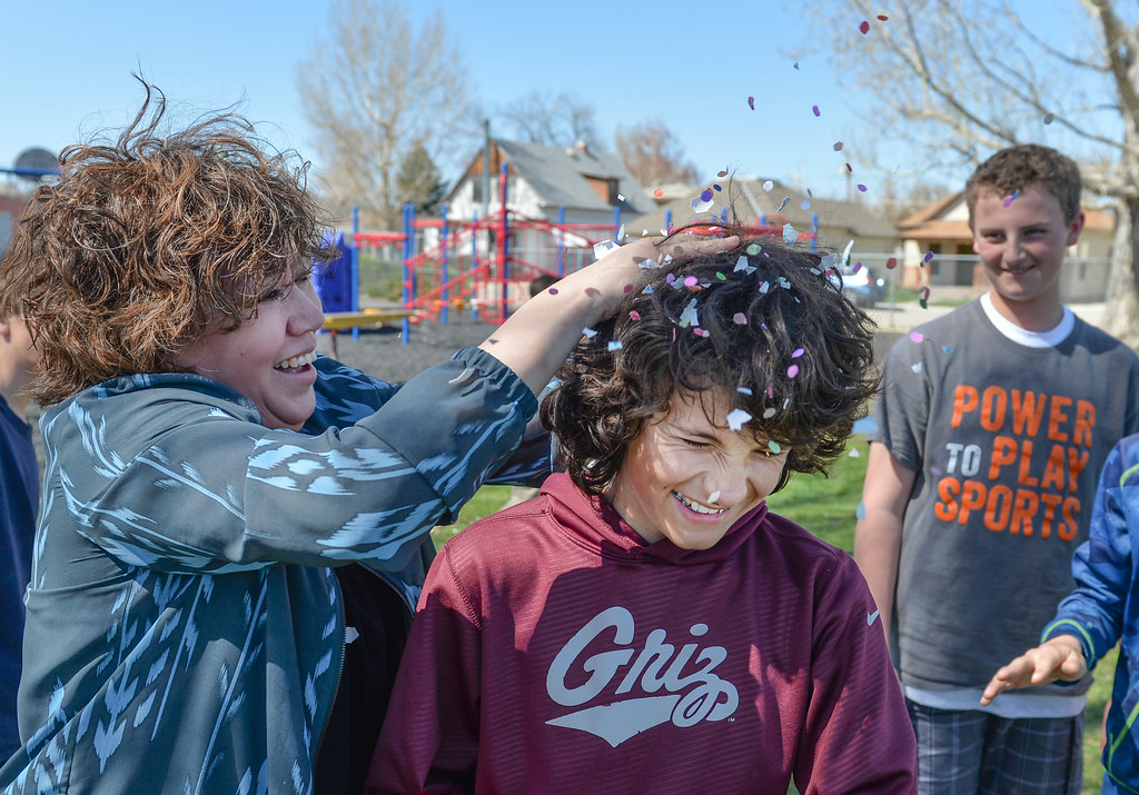 Justin Sheely | The Sheridan Press<br /> Spanish teacher Maria Montano cracks a Mexican Cascarones Easter Egg over Aiden Roth Thursday at Holy Name Catholic School. Students from spanish language studies made the cascarones by emptying eggs then filling them with confetti. The confetti-filled eggs are part of hispanic tradition that involves cracking the eggs over a person's head. The showering of the confetti is said to bring good luck and good fortune to the recipient. In a religious context, the eggs represent the empty tomb and the resurrection of Jesus.