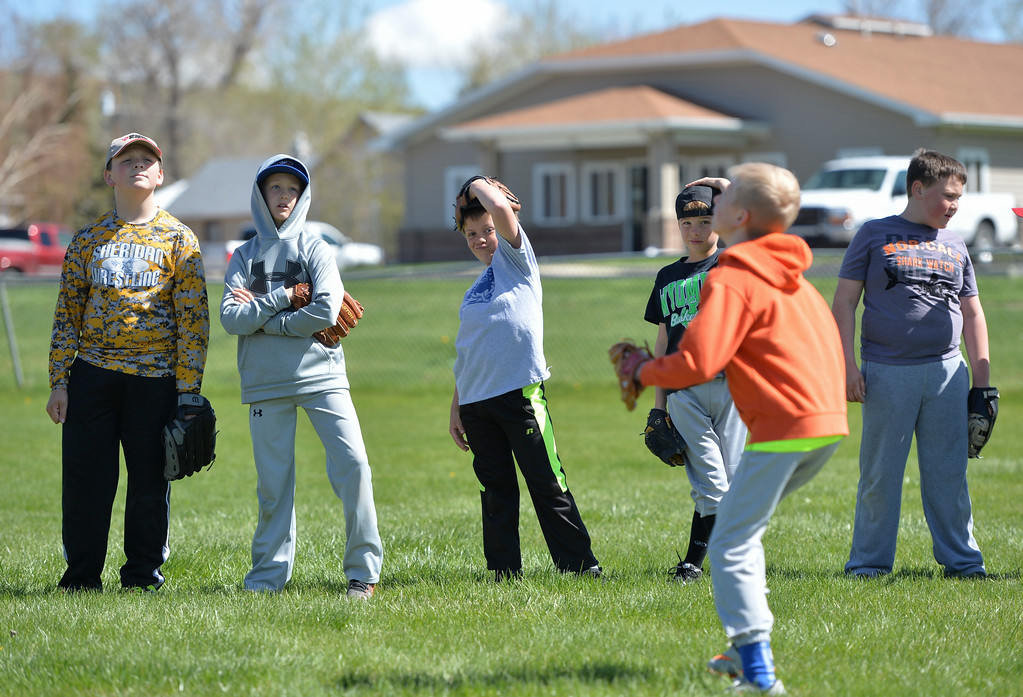 Justin Sheely | The Sheridan Press<br /> Students watch as others catch fly balls during Sheridan Recreation District's Spring Baseball Clinic Saturday at Oatts Field in Sheridan.