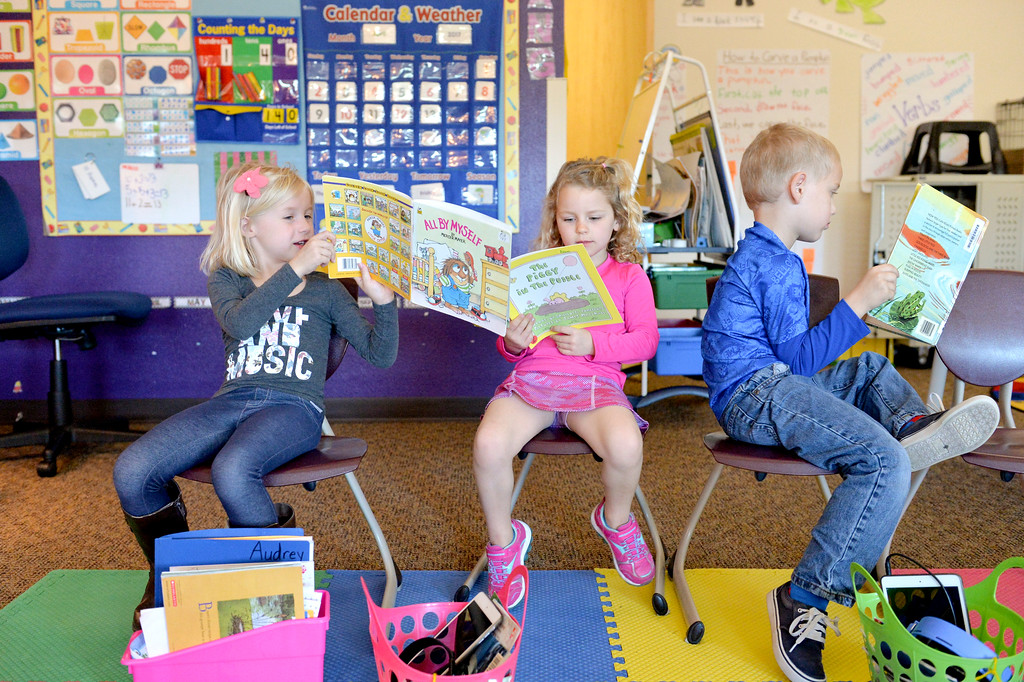 Justin Sheely | The Sheridan Press<br /> Kindergartners, from left, Audrey Sisson, Lakely Treide and Riley Wagner read during literacy time Thursday at Woodland Park Elementary School. The school will be piloting full-day kindergarten this fall, opposed to the currently early out schedule for kindergarten classes already in practice in the school district.