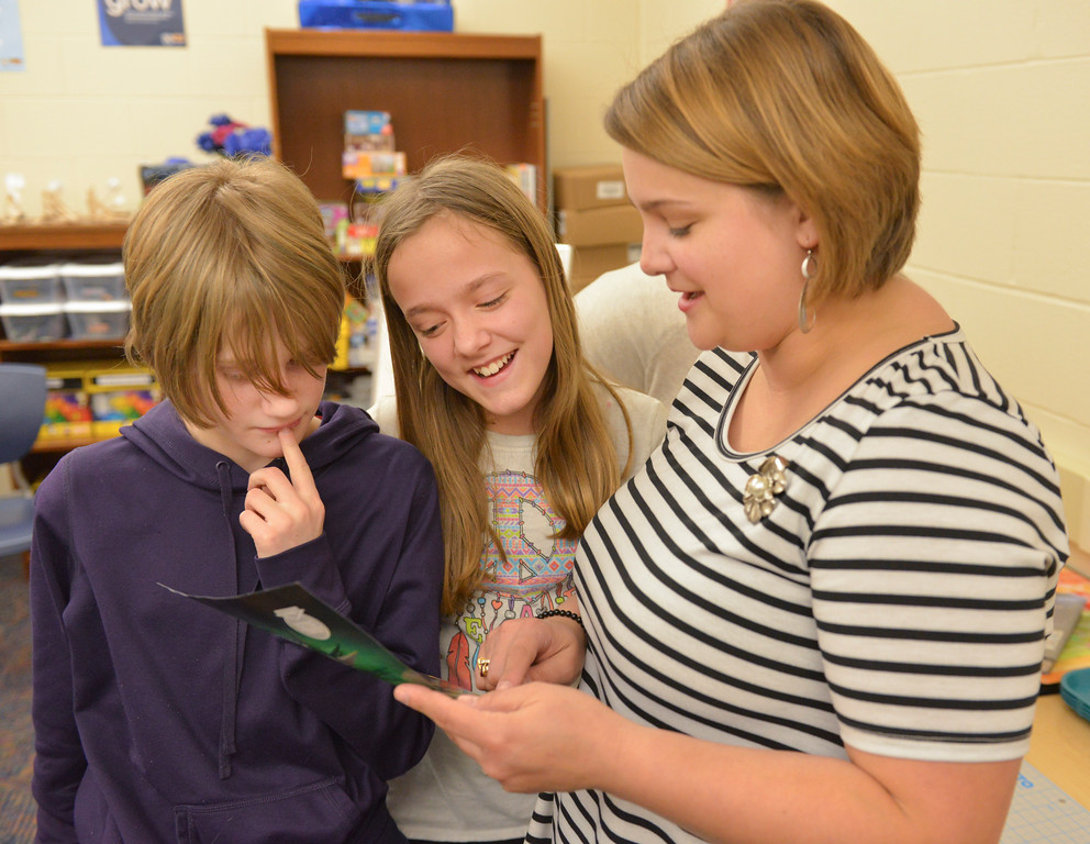"Justin Sheely | The Sheridan Press<br /> Middle schoolers Myra Fuhrman, left, and Torance Sorenson look at a student's collage project with after school teacher Emily Swinyer during the after school program ""Mixed Media Collage"" Thursday at Sheridan Junior High School."