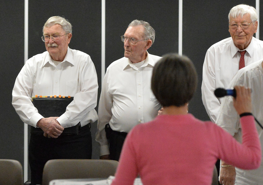 """Justin Sheely   The Sheridan Press<br /> Choir members, from left, Terry Peters, Leonard Hurst and John Trohkimoinen stand as the others enter the stage during the Sheridan Aires performance """"Sing into Spring"""" at The Hub on Smith Thursday, April 5, 2018."""