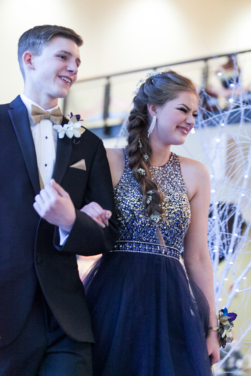 Tibby McDowell   The Sheridan Press Eli Phillips, left, and his date Carley Motsick giggle at the announcers comments as they cross the stage during the Big Horn High School Prom at the Whitney Academic Center at Sheridan College Saturday, April 7, 2018.