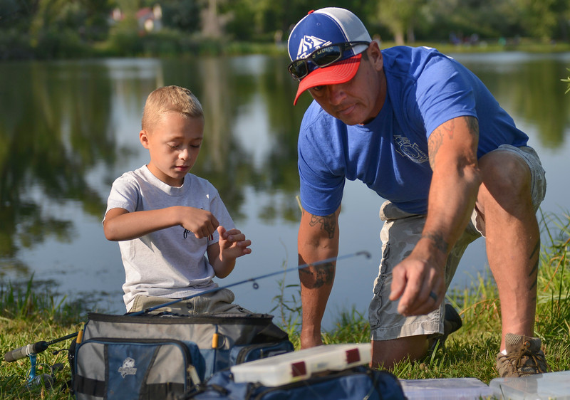 Justin Sheely | The Sheridan Press<br /> Seven-year-old Camdin Miles baits a hook with Bryan Smith during the annual Fishing Derby at Rotary Pond in Ranchester Saturday, Aug. 4, 2018. The Tongue River Valley Community Center hosted the fishing derby for children under 13 and under. Children competed for most fish caught and biggest catch to win prizes.