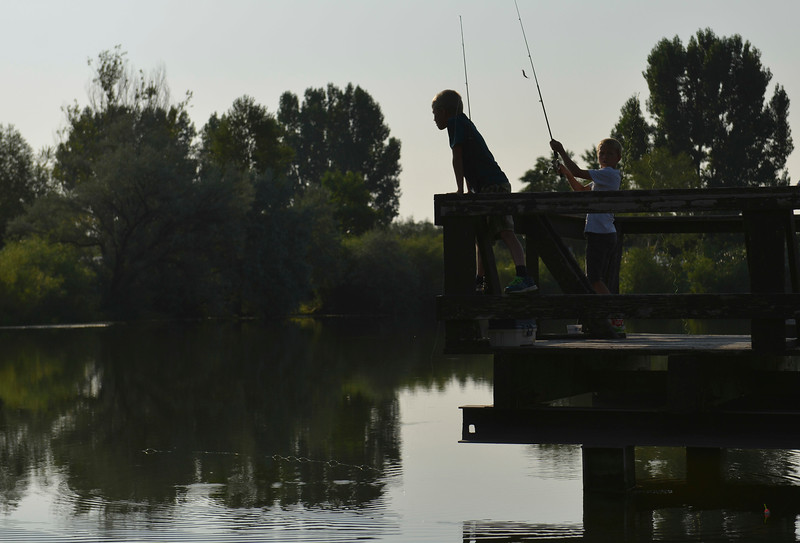 Justin Sheely | The Sheridan Press<br /> Children reel in their lines during the annual Fishing Derby at Rotary Pond in Ranchester Saturday, Aug. 4, 2018. The Tongue River Valley Community Center hosted the fishing derby for children under 13 and under. Children competed for most fish caught and biggest catch to win prizes.